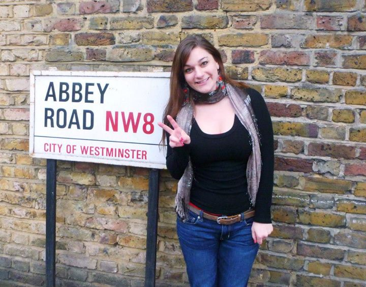 Leah Zarra posing in front of a sign for the famous Abbey Road.